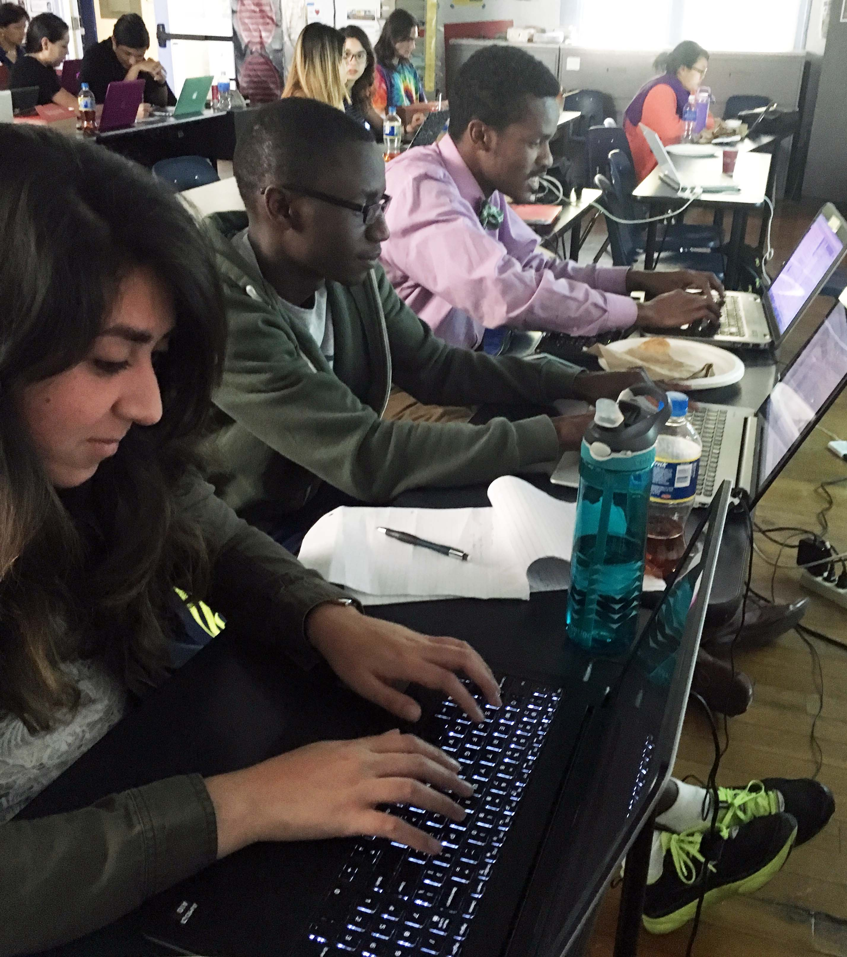 Photo of students using their computers to code in python